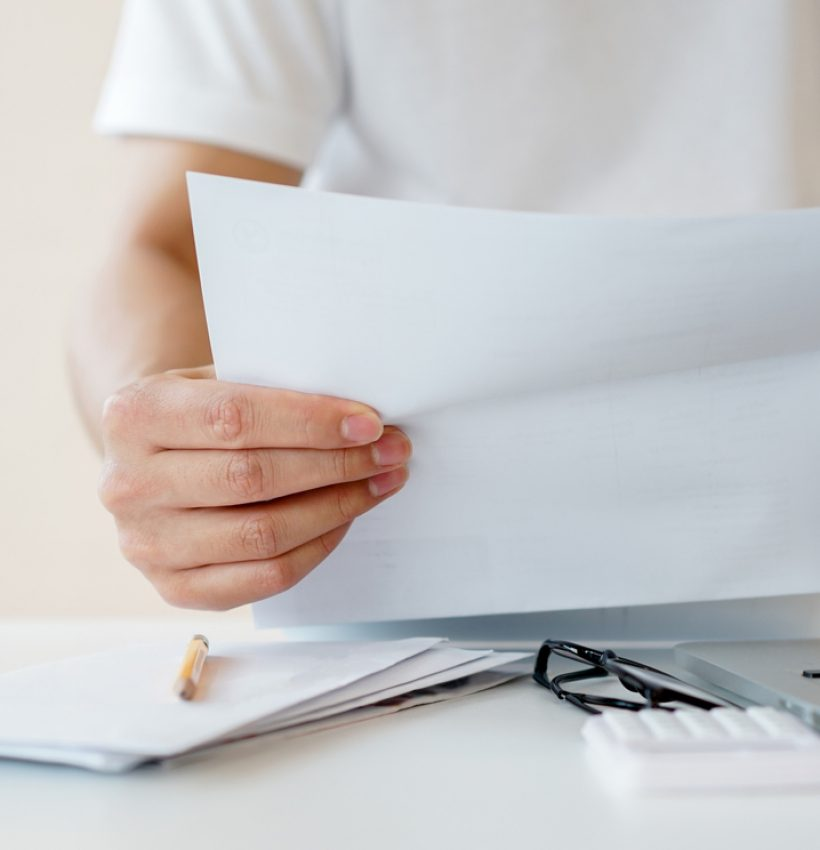 close up man hand holding invoice paper form mail to reading and check list of spending of the month and planing to manage money for financial and life concept