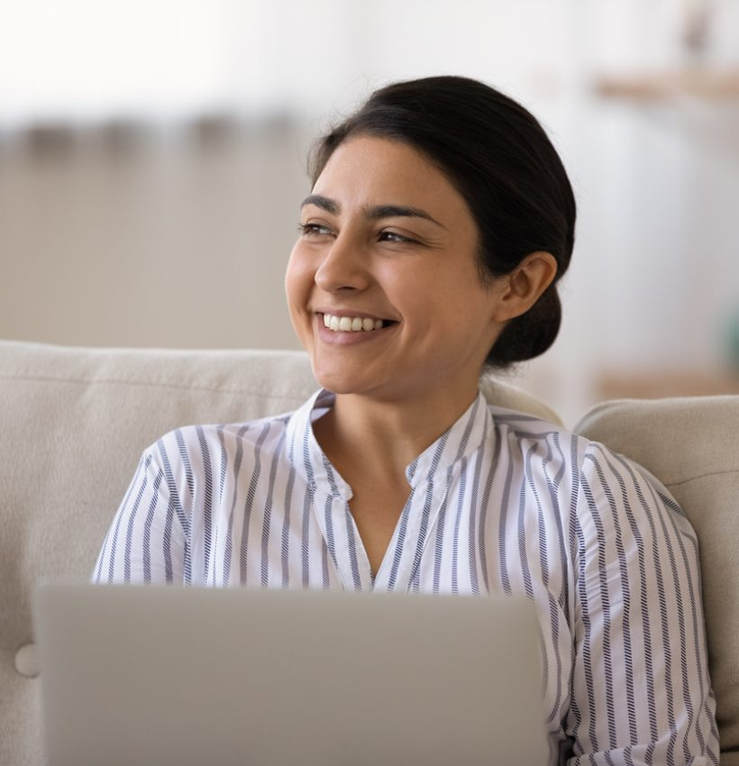 Smiling young Indian woman use laptop look in distance thinking or dreaming or perspectives achievements. Happy mixed race female work online on computer make plans. Business vision concept.